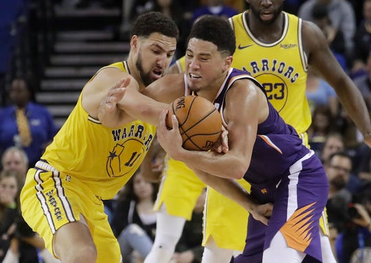 Phoenix Suns guard Devin Booker, right, tries to hold onto the ball as he is defended by Golden State Warriors guard Klay Thompson during the second half of an NBA basketball game in Oakland, Calif., Sunday, March 10, 2019. (AP Photo/Jeff Chiu)