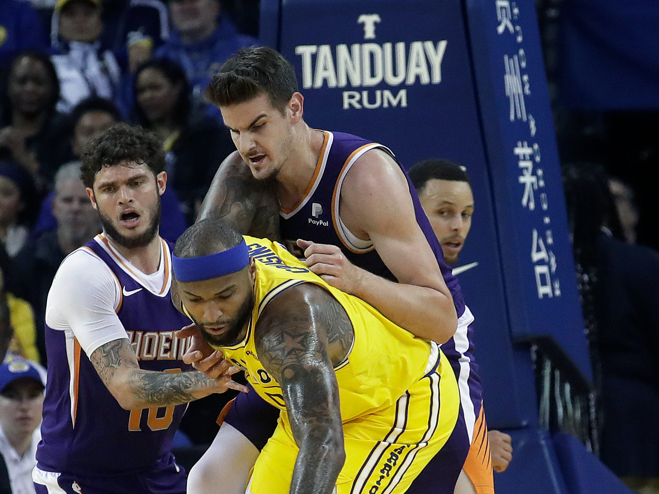 Golden State Warriors center DeMarcus Cousins, center, reaches for the ball in front of Phoenix Suns guard Tyler Johnson, left, and forward Dragan Bender during the first half of an NBA basketball game in Oakland, Calif., Sunday, March 10, 2019. (AP Photo/Jeff Chiu)