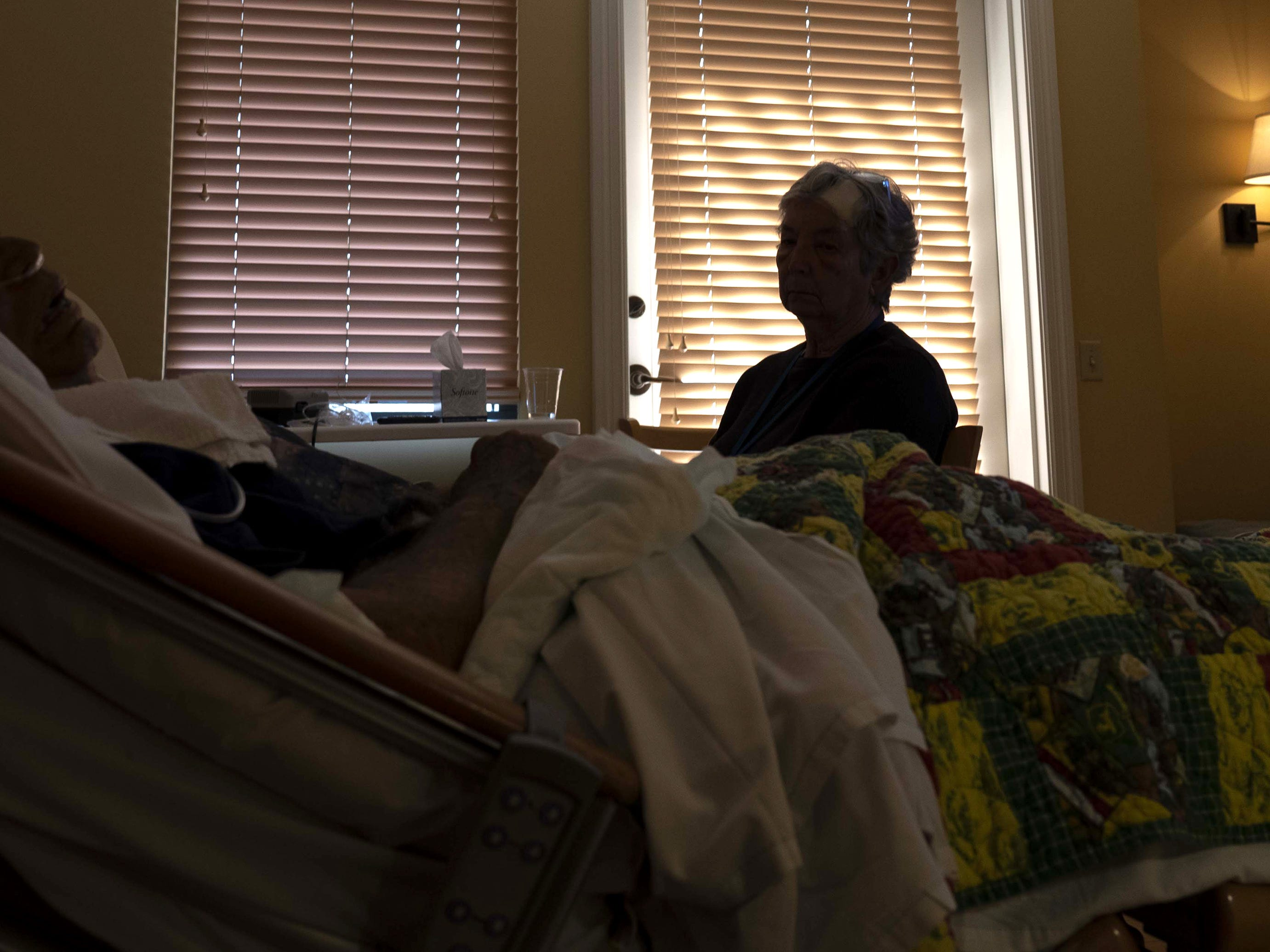 Jane Conrow, a volunteer with Hospice of the Valley's 11th Hour Companion program, watches patient Robert Arneson.
