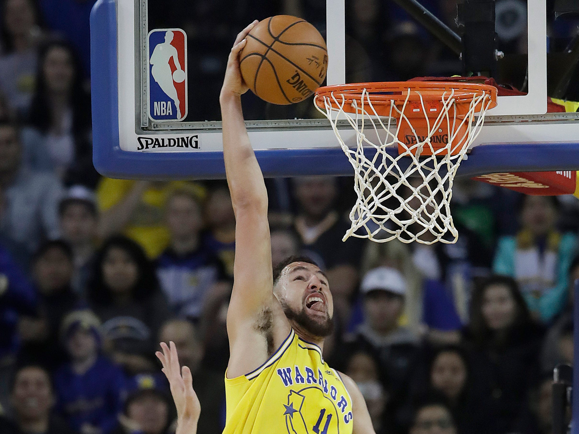 Golden State Warriors guard Klay Thompson (11) dunks over Phoenix Suns forward Dragan Bender, left, and guard Devin Booker during the first half of an NBA basketball game in Oakland, Calif., Sunday, March 10, 2019. (AP Photo/Jeff Chiu)