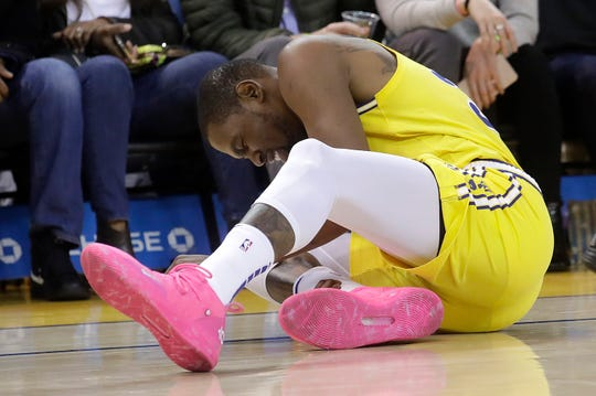 Golden State Warriors forward Kevin Durant reacts after injuring his ankle during the second half of an NBA basketball game against the Phoenix Suns in Oakland, Calif., Sunday, March 10, 2019. (AP Photo/Jeff Chiu)