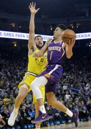 Phoenix Suns guard Devin Booker (1) shoot against Golden State Warriors guard Klay Thompson (11) during the first half of an NBA basketball game in Oakland, Calif., Sunday, March 10, 2019. (AP Photo/Jeff Chiu)