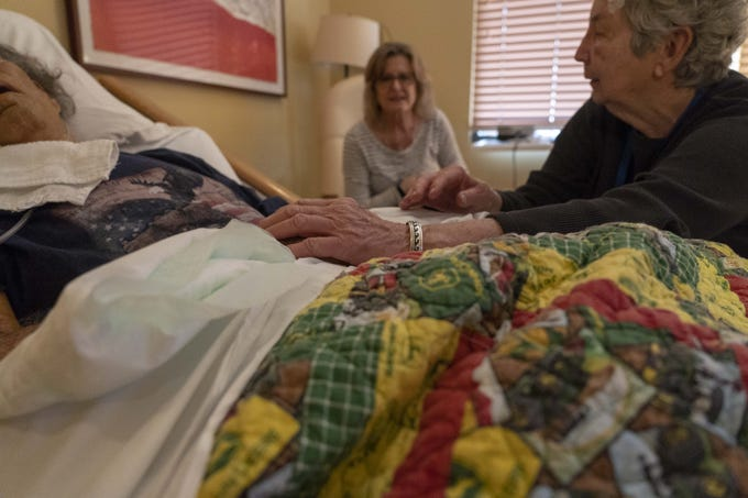 """Jane Conrow, right, a volunteer with Hospice of the Valley's 11th Hour Companion program, and Lynn Tolmachoff, center, watch patient Robert Arneson. The hospice's program sends volunteers to the bedside of patients who are """"actively dying,"""" giving grieving families a break and ensuring no patient dies alone."""