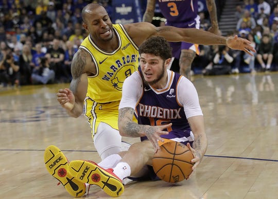 Phoenix Suns guard Tyler Johnson, right, tries to control the ball on the floor as he is guarded by Golden State Warriors guard Andre Iguodala during the second half of an NBA basketball game in Oakland, Calif., Sunday, March 10, 2019. (AP Photo/Jeff Chiu)