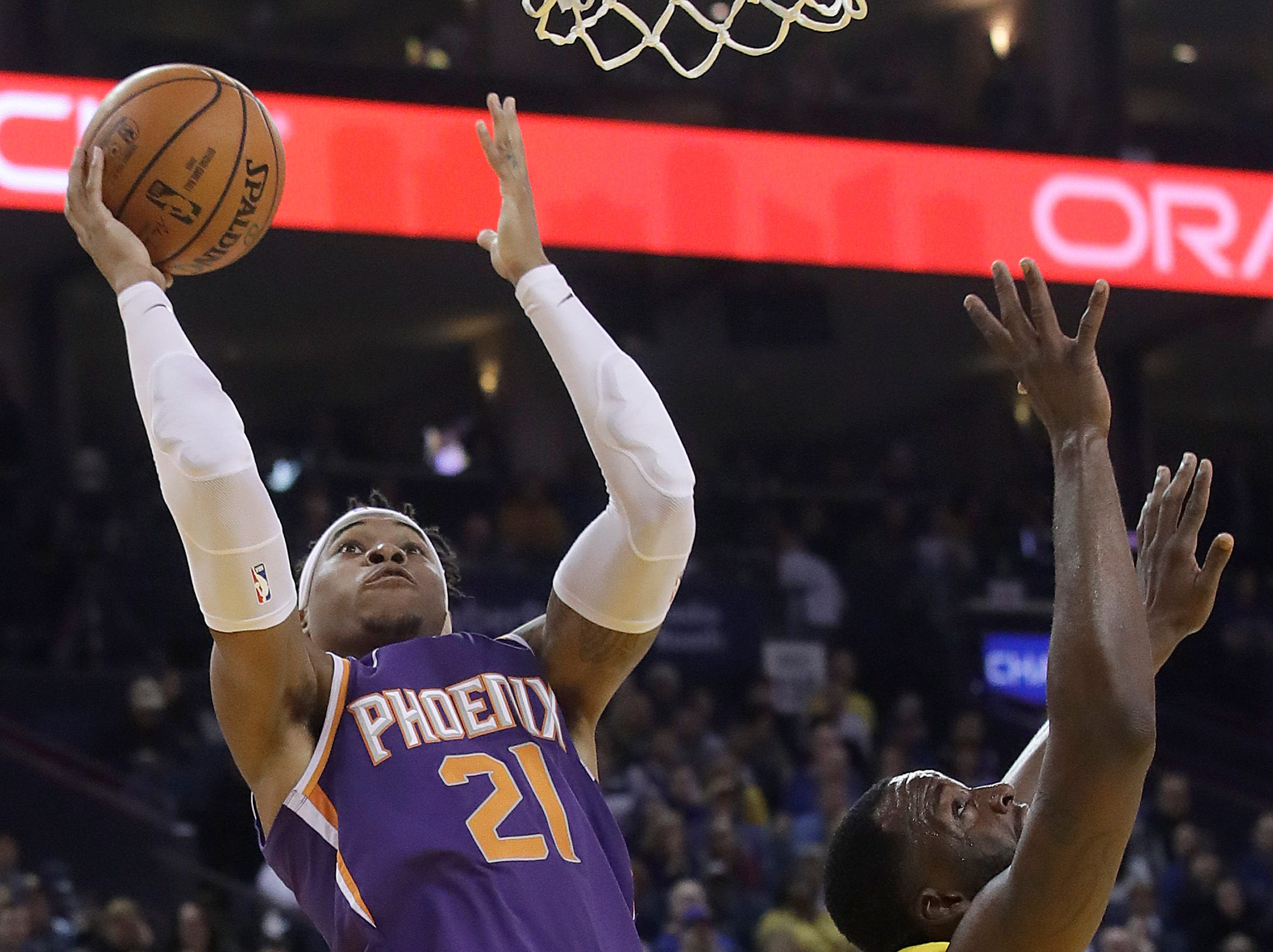 Phoenix Suns forward Richaun Holmes, left, shoots against Golden State Warriors forward Draymond Green, right, during the first half of an NBA basketball game in Oakland, Calif., Sunday, March 10, 2019. (AP Photo/Jeff Chiu)