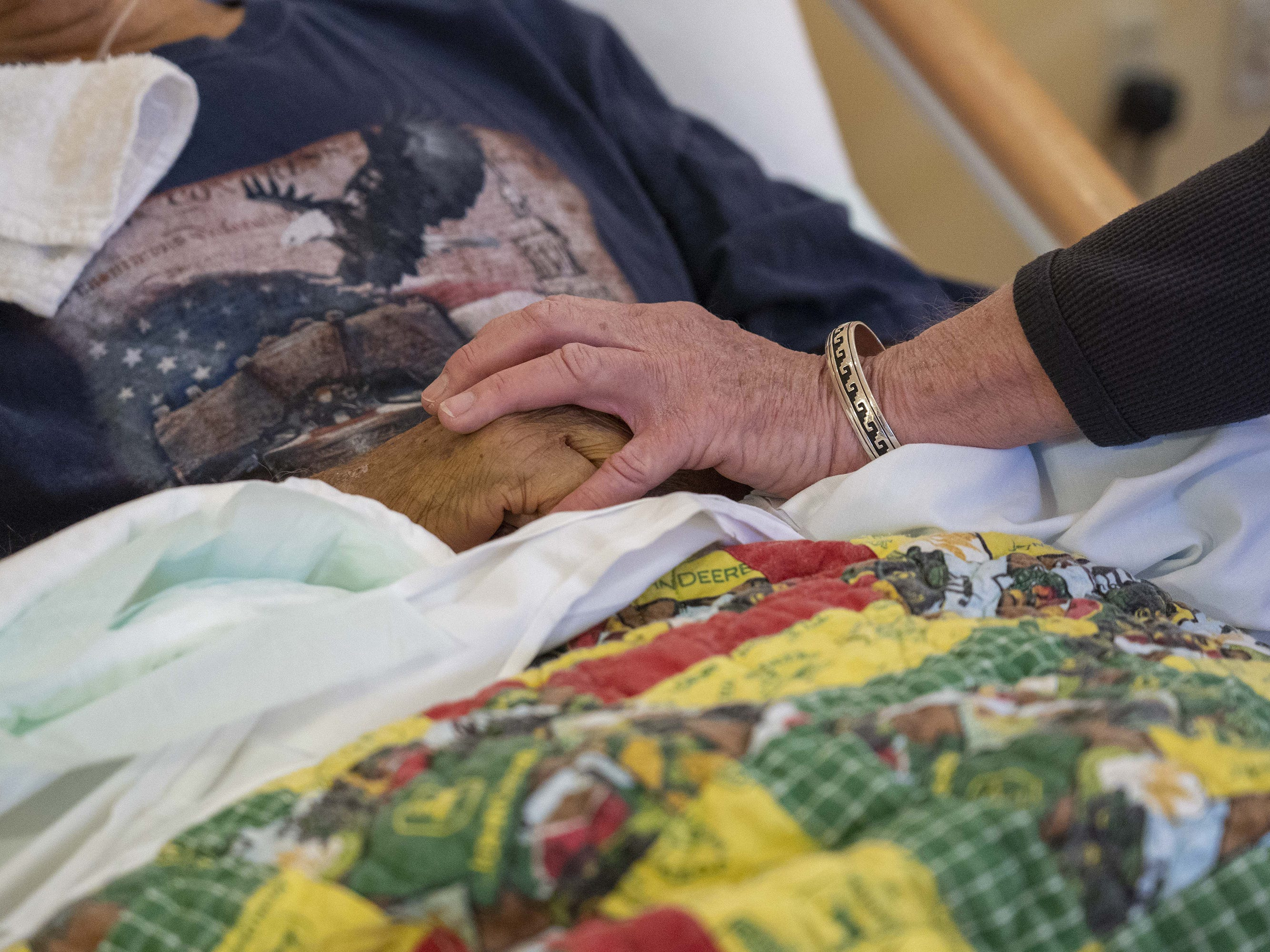 """Jane Conrow touches Robert Arneson's. Conrow, a volunteer with 11th Hour Companions, likes to tell patients, """"You're not alone. I'm right here with you."""""""