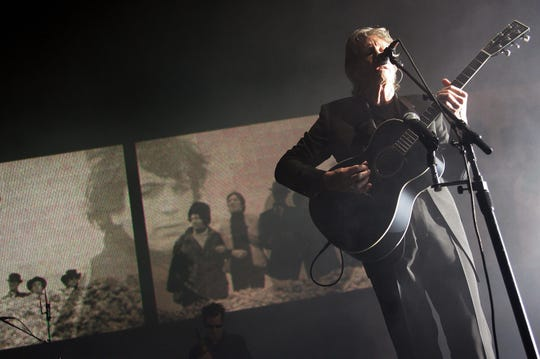 British rock legend Roger Waters, co-founder of the group Pink Floyd, sings during a performance at Hong Kong's Convention and Exhibition Centre, 15 February 2007, as an image of the late Syd Barrett (L), the other co-founder and original member of Pink Floyd, is projected on the back screen.