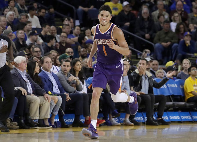 Phoenix Suns guard Devin Booker (1) gestures after scoring against the Golden State Warriors during the second half of an NBA basketball game in Oakland, Calif., Sunday, March 10, 2019. (AP Photo/Jeff Chiu)