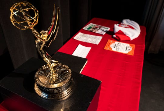 "An Emmy Award stands on a table next to hockey memorabilia before Mike ""Doc"" Emrick begins his Port Huron Town Hall speech Monday, March 11, 2019 at McMorran Theater. Emrick won the Emmy for Outstanding Sports Personality - Play-By-Play in 2017."