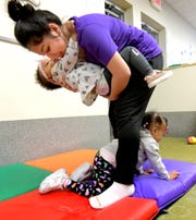 Crispus Attucks Charter School student Alondra Hernandez holds Leilani Smallwood while Zoey Wilson crawls at Crispus Attucks Early Learning Center Monday, March 11, 2019. Both children are 1. Crispus Attucks Charter School students and graduates gain experience at the center while working toward childcare certification. Bill Kalina photo