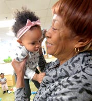 Crispus Attucks Early Learning Center assistant teacher Deb Gray holds Leilani Smallwood, 1, at the center Monday, March 11, 2019. Crispus Attucks Charter School students and graduates gain experience at the center while working toward childcare certification. Bill Kalina photo