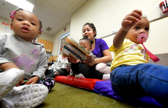 Crispus Attucks Charter School student Alondra Hernandez prepares to read to children, from left, Zoey Wilson, Alani McCowin and Dream Martino, all 1, at Crispus Attucks Early Learning Center Monday, March 11, 2019. Crispus Attucks Charter School students and graduates gain experience at the center while working toward childcare certification. Bill Kalina photo