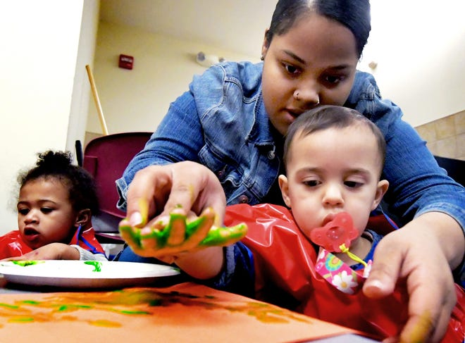 Crispus Attucks Charter School student Nai-Agah Martino works with Olivia Fedor, 2, and Layla Park, 1, left, while hand painting at Crispus Attucks Early Learning Center Monday, March 11, 2019. Crispus Attucks Charter School students and graduates gain experience at the center while working toward childcare certification. Bill Kalina photo