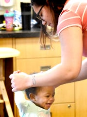 Crispus Attucks Early Learning Center assistant group supervisor Alexus Eaton plays with Kennedi Johnson, 11 months, at the center Monday, March 11, 2019. Crispus Attucks Charter School students and graduates gain experience at the center while working toward child care certification. Bill Kalina photo