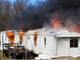 Flames shoot from a trailer in the 2700 block of Genna Circle in Dover Township on Monday afternoon.