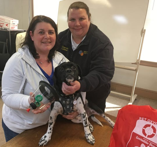 Kristine Wheeler, left, and Tipper – a bulldog and cocker spaniel mix – demonstrate how to use the pet oxygen mask donated to Grantley EMS. Capt. Kim Lindner, of Grantley EMS, assists.