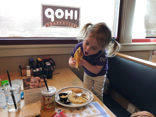 Three-year-old Naomi Bakker of Reno hoists a pancake mouthward at IHOP in South Reno. Bakker, born weighing less than 13 ounces, now is thriving after receiving care at Renown Children's Hospital, which benefits from donations made on IHOP's Free Pancake Day, March 12, 2019.
