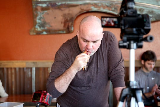 Max Carnage, winner of the Adam's Rib Smokehouse Goliath burger eating contest, finishes the final scraps of his burger while recording his progress in Salem on Saturday, March 2, 2019.