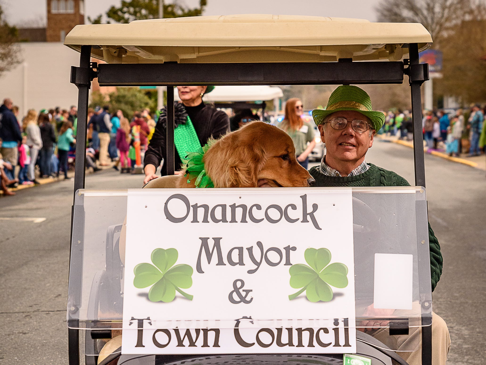 Onancock Mayor Fletcher Fosque shares his golf cart with man's best friend during the St. Patrick's parade on Sunday.