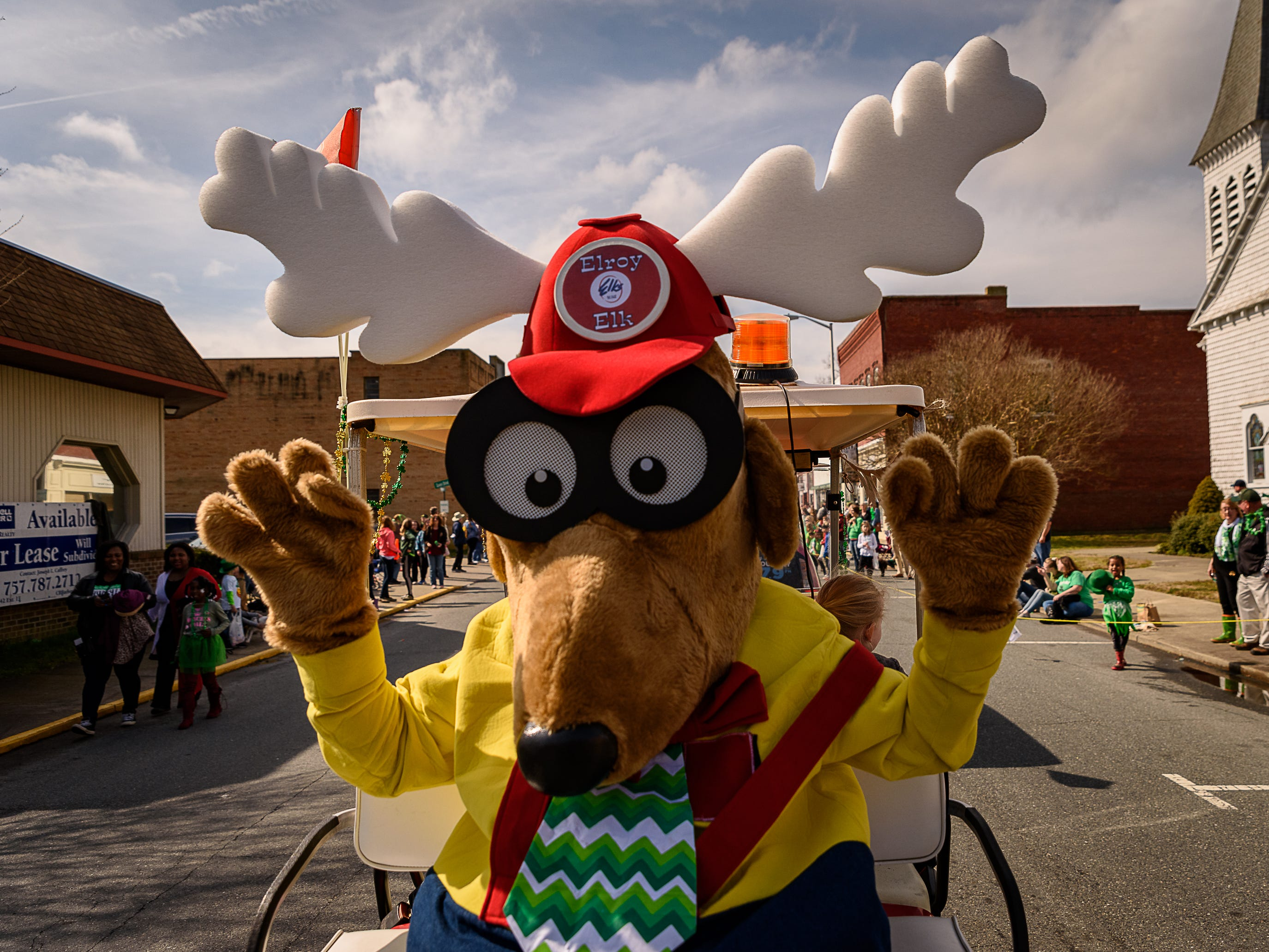 Elroy Elk. the local Elks Club mascot, rides a golf cart through downtown Onancock in the St. Patrick's parade.