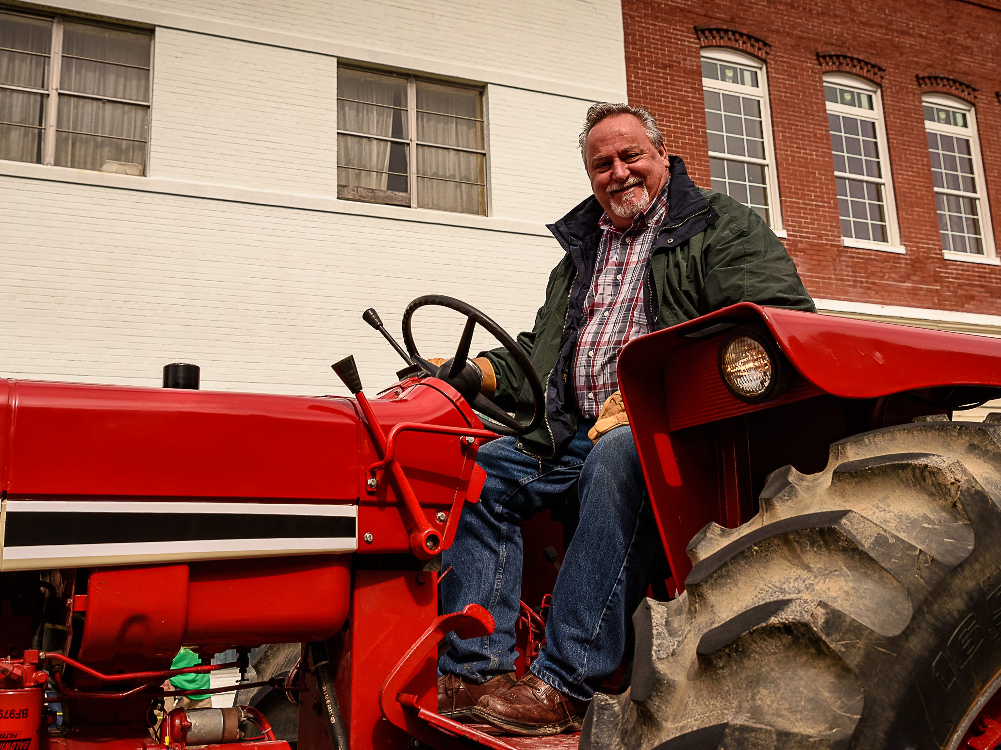 A member of the Peninsula Tractor Organization  shows off his vintage tractor during the Onancock parade.