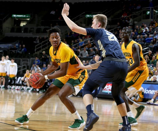 Tyree Eady from North Dakota State looks to pass while defended by Chaz Schneider of Oral Roberts at the 2019 Summit League Basketball Tournament at the Denny Sanford Premier Center in Sioux Falls.