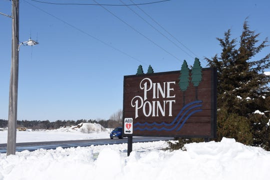 The sign to Pine Point neighborhood displays a sign denoting the nearest AED.