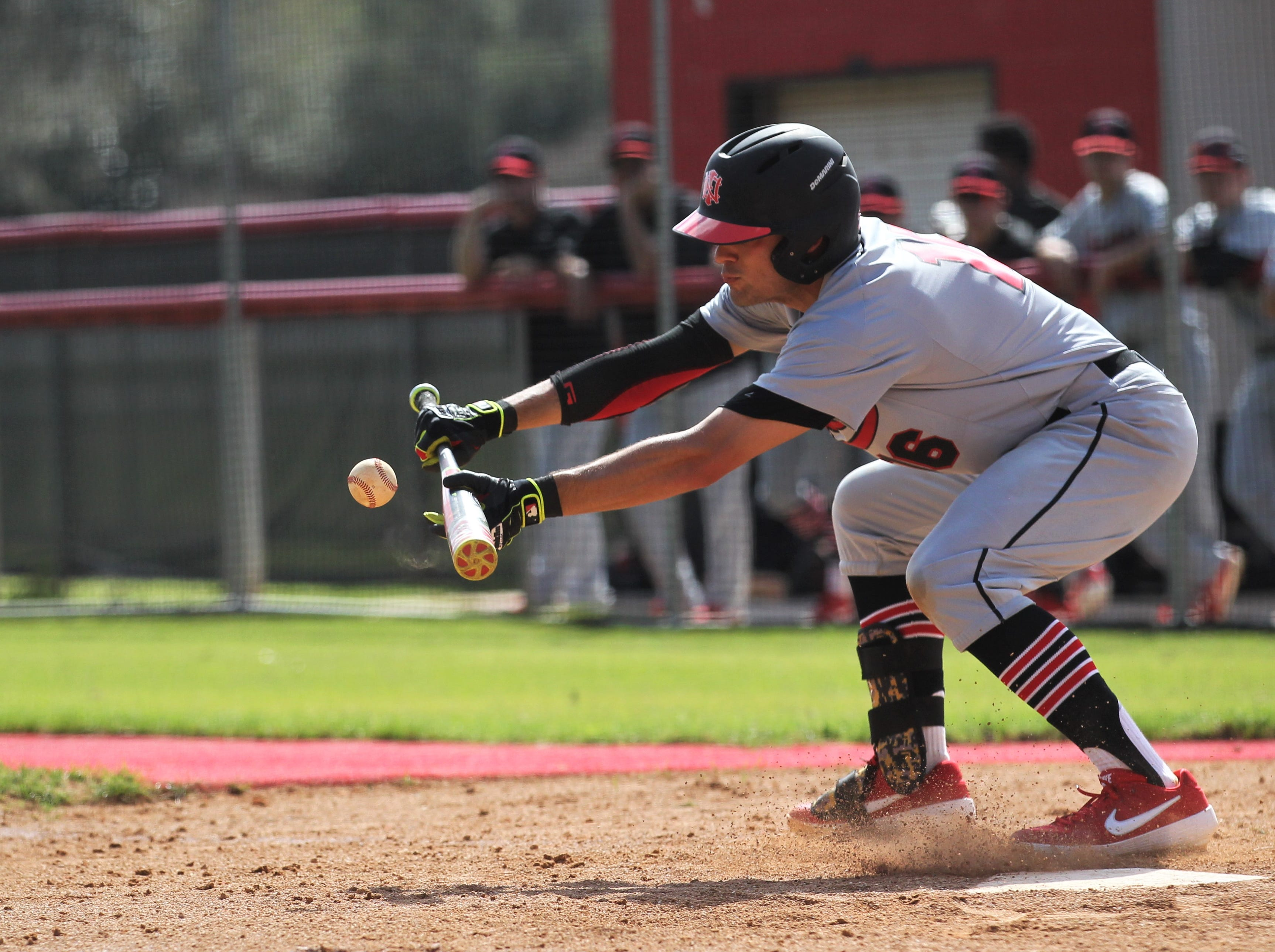 NFC senior Josiah Miller drops down to bunt during a preseason game at Leon. Miller, an FSU signee, transferred from Lincoln for his final high school season.