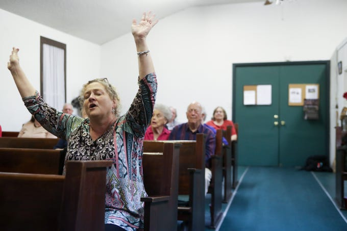 Kay Ganey puts her arms up in sync with a song being sung by her friend Risa Powell during the last gospel sing service at Ole Gospel Tabernacle Church Friday, March 8, 2019.