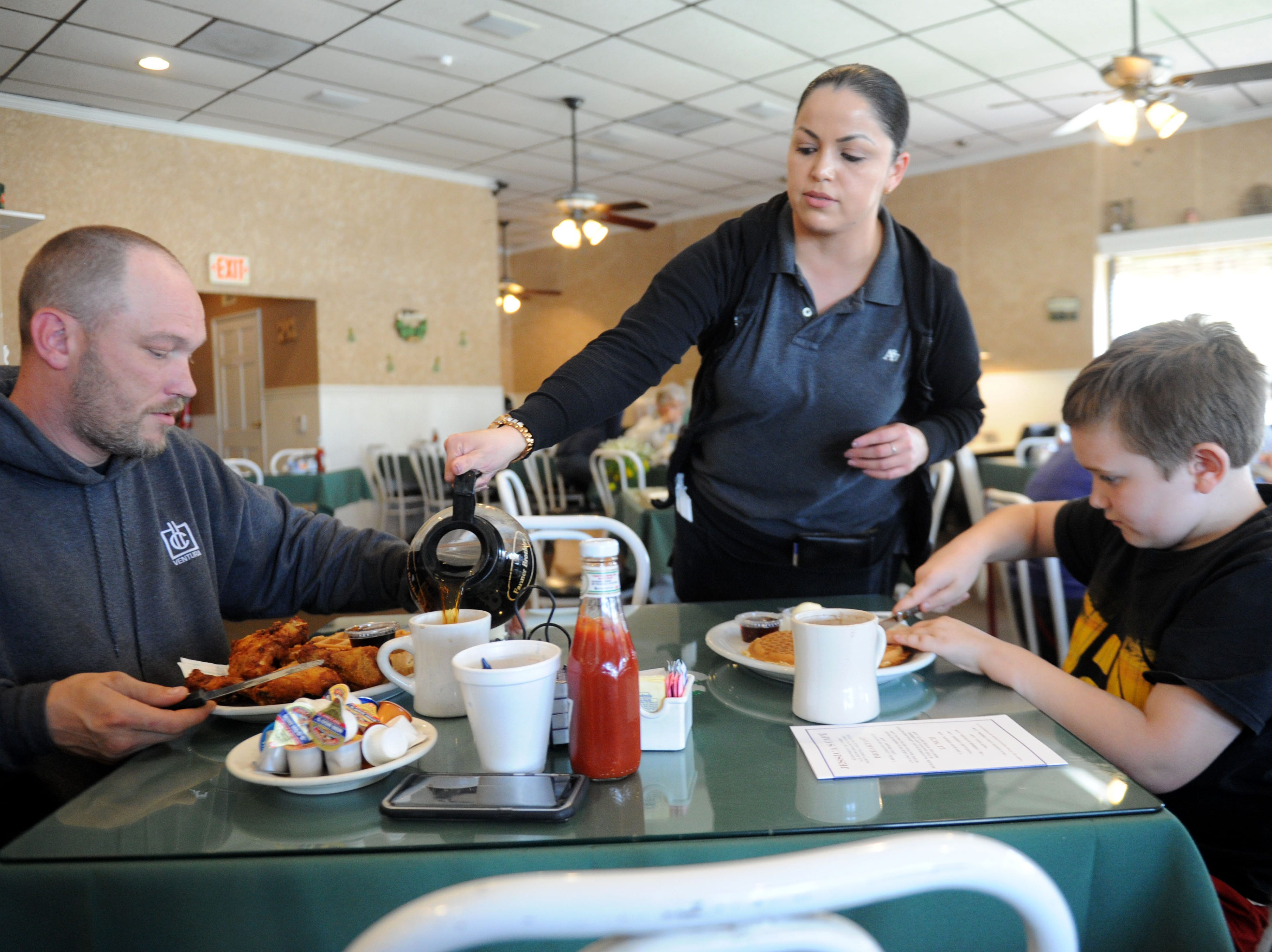 Michael Aldridge and his son Camren Aldridge, 9,  are helped by waitress Karina Martinez at Jessica's Cafe in Camarillo.
