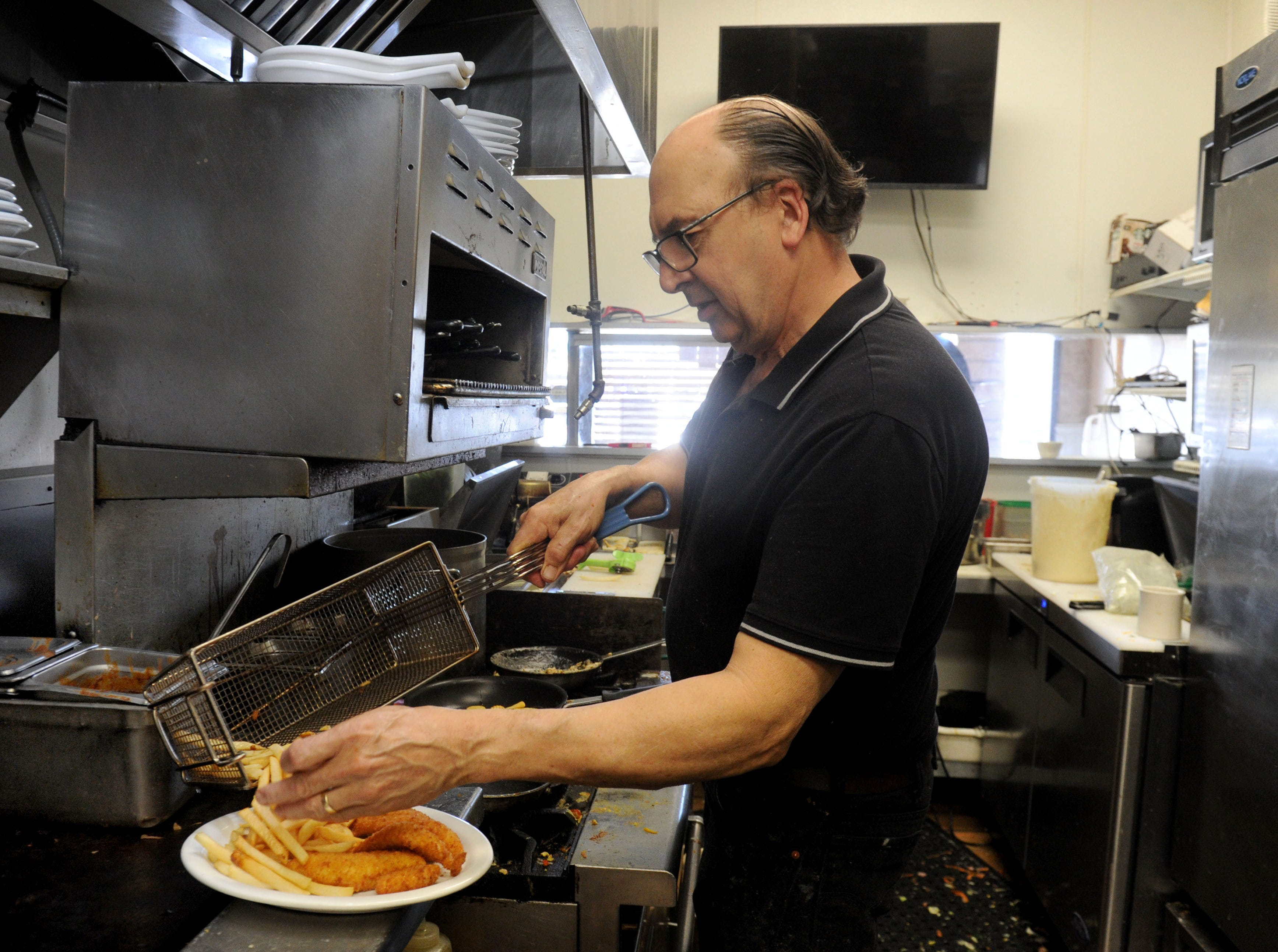 Thomas Fontes, owner and chef of Jessica's Cafe in Camarillo plates an order of fish with French fries.