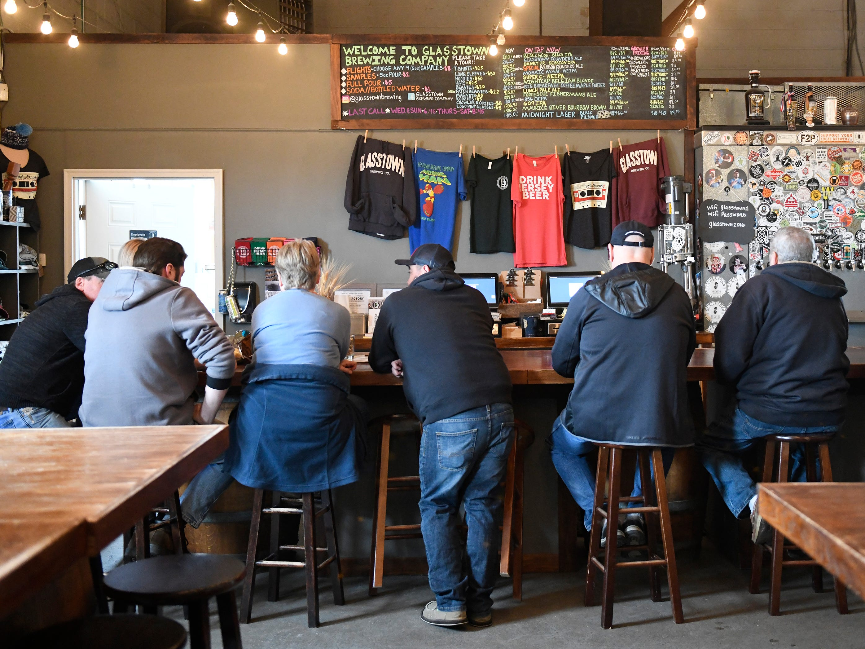 Patrons sit at the bar at Glasstown Brewing Company in Millville on Friday, March 8, 2019.