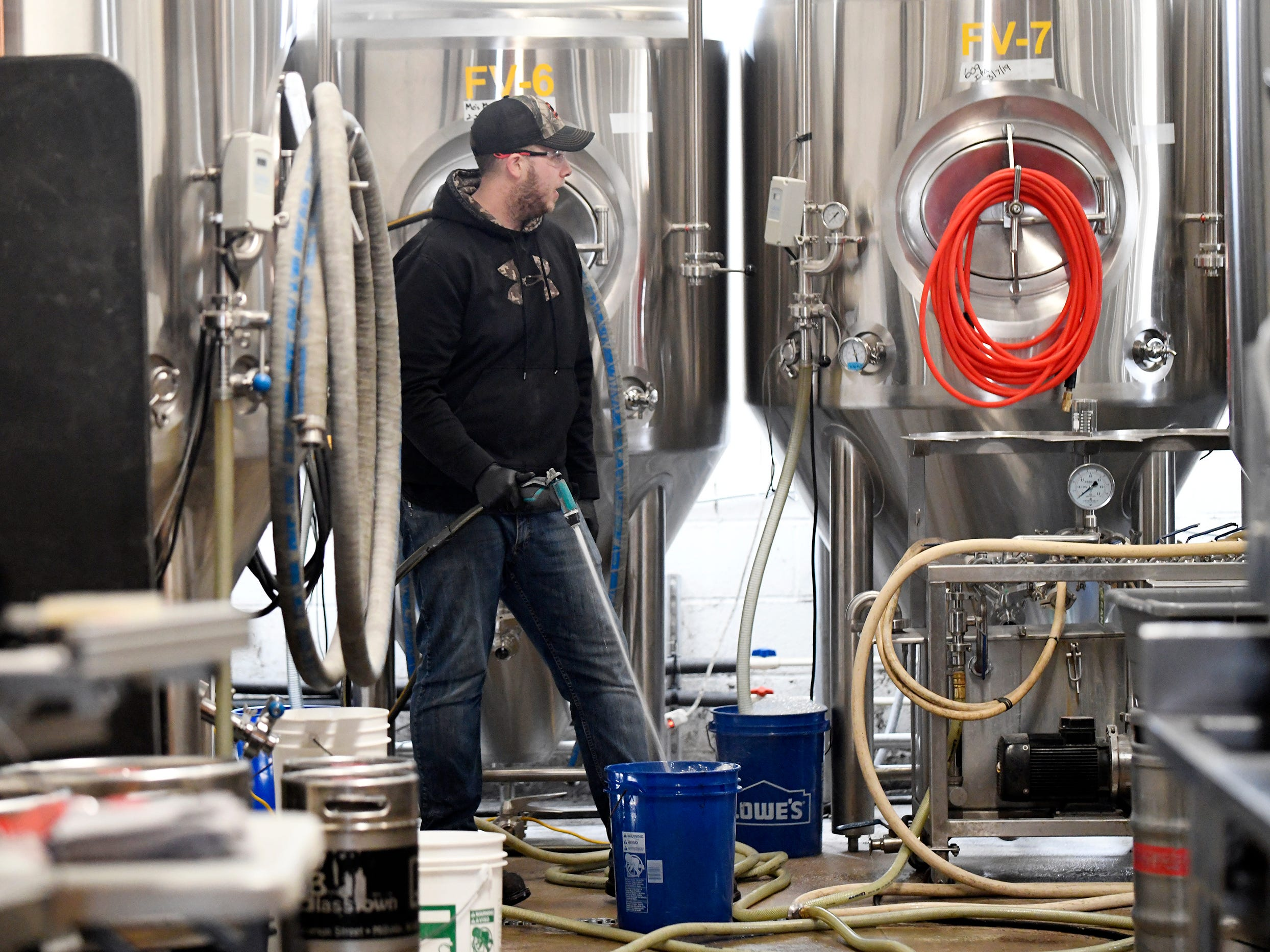 Staff at Glasstown Brewing Company in Millville clean up after making one of their signature beers on Friday, March 8, 2019.