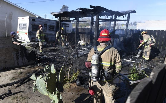 Visalia firefighters at the scene of a shed fire near Santa Fe Street and Houston Avenue on Monday, March 11, 2019.  A fence near the shed was charred.