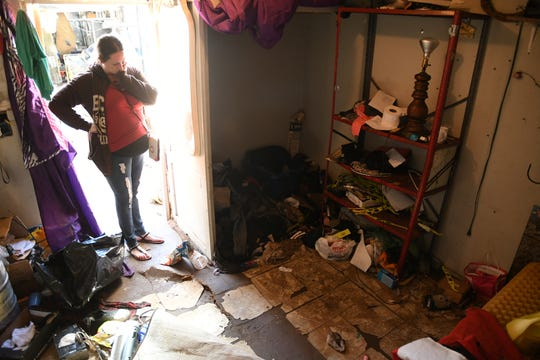 Charisma Owens surveys the remains of her condemned home in Strathmore, after a severe flood filled the residence with several inches of septic-contaminated water.
