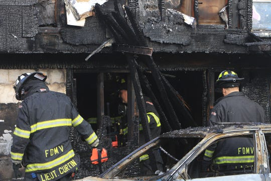 Mount Vernon firefighters work at the scene of a 2013 fatal fire in the city. Four members of one family died.