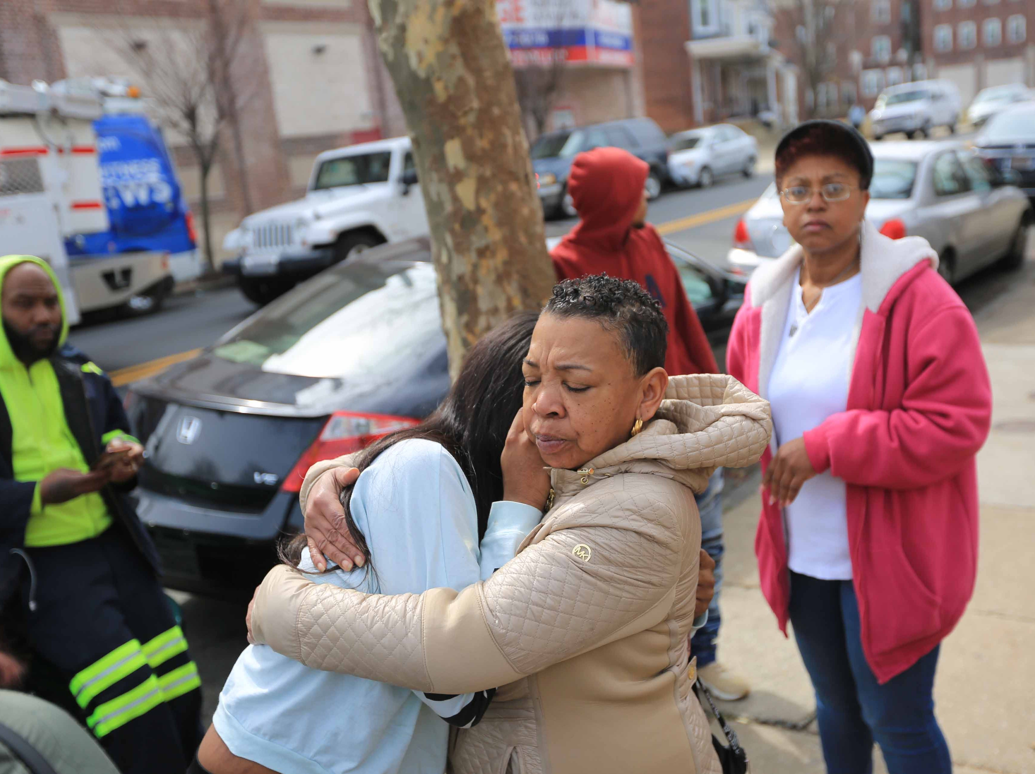 Members of the community embrace while police continue to investigate the crime scene on W. 26th and N. Market St. where two 17-year-olds were fatally shot Monday morning.