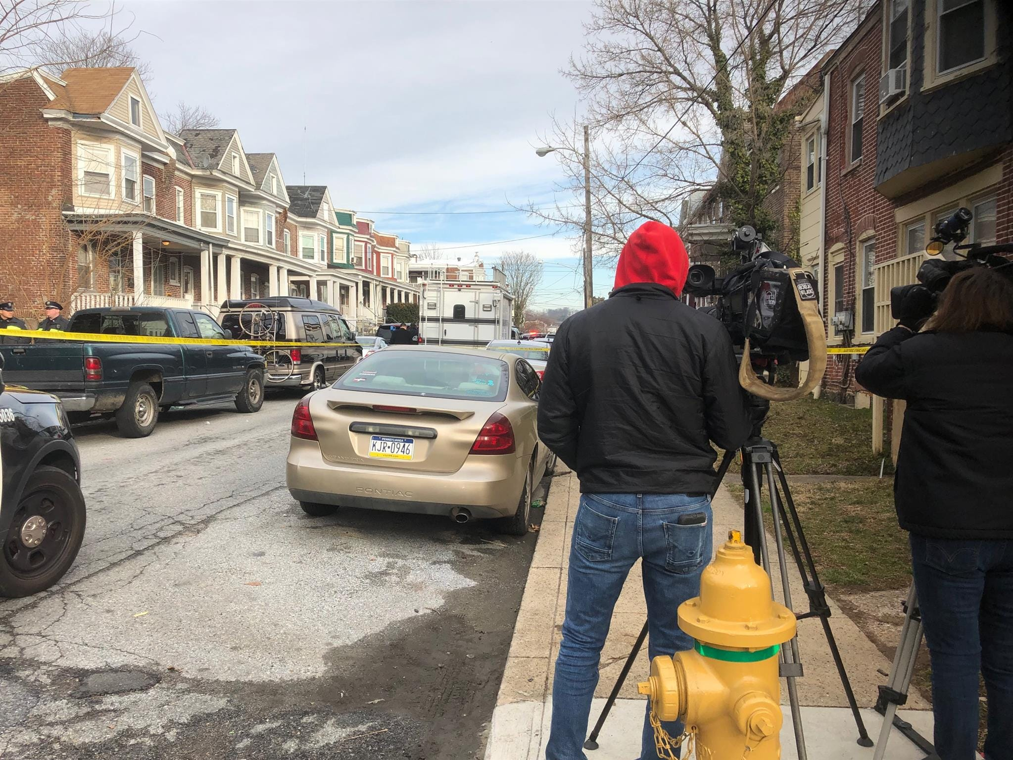 Police have the scene of a double homicide taped off on West 26th Street in Wilmington on Monday, March 11, 2019, while neighbors and news crews wait nearby for details.