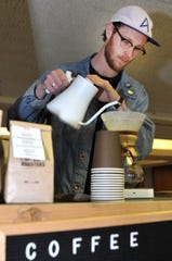 Loft Roasters Coffee CEO, Mason Wilson, brews a cup of coffee using a Chemex method of making coffee, Monday afternoon. Wilson said they are looking to create an atmosphere that encourages meaningful conversations.
