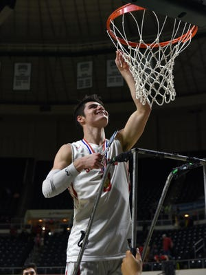 Ethan Heller smiles as he cuts down the net following Sheridan's 59-44 win against Jackson in a Division II district final at The Convocation Center. Heller scored a game-high 29 points as the Generals reached their first regional tournament in 19 years.