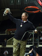Sheridan coach Doug Fisher hoists the net from Sunday's Division II district final win against Jackson. The Generals will play Steunbenville on Wednesday in their first regional appearance since 2000.