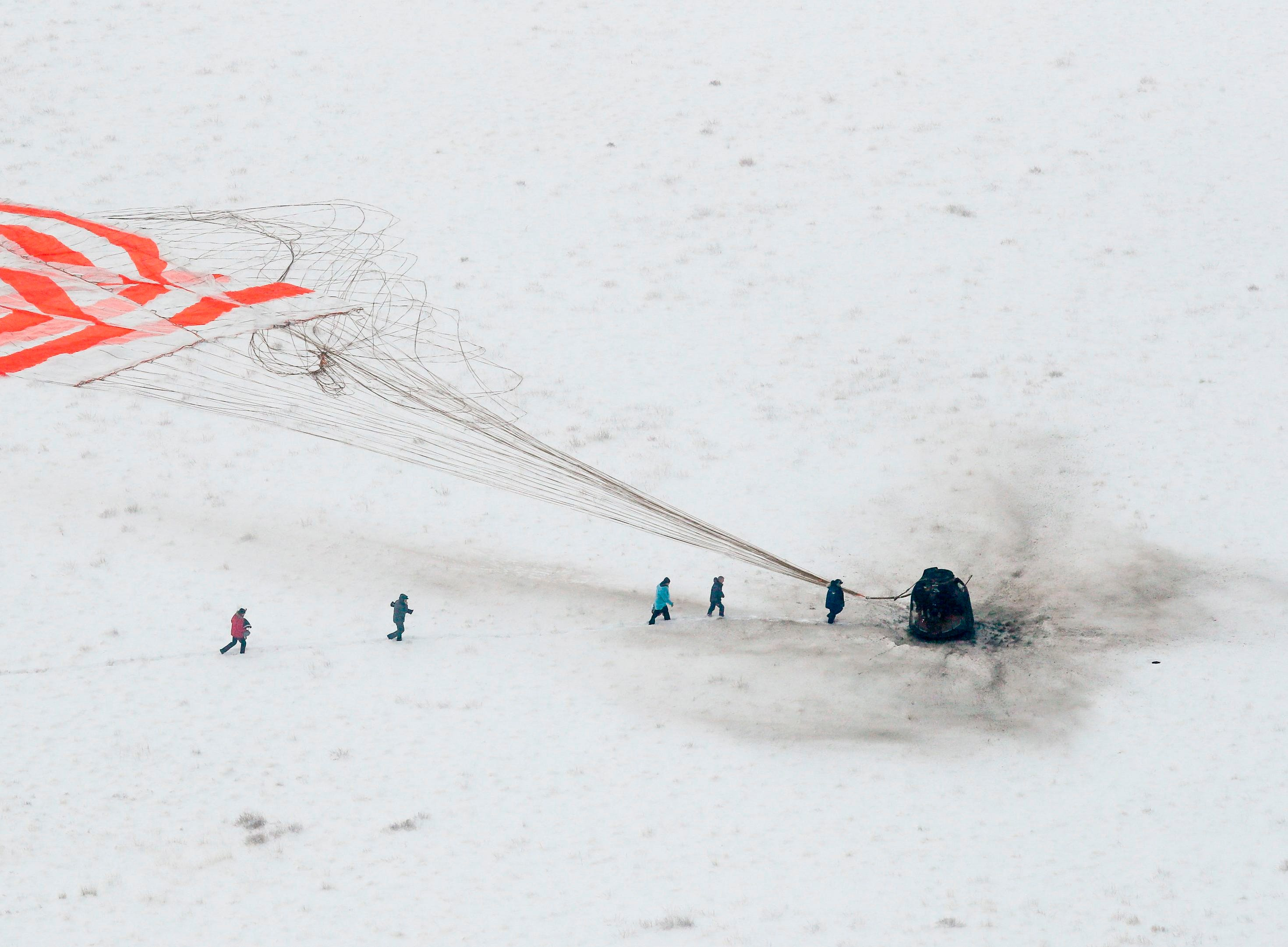 A search and rescue team approaches the Soyuz MS-09 capsule carrying the International Space Station crew after its landing in a remote area outside the town of Dzhezkazgan Kazakhstan, Dec. 20, 2018.