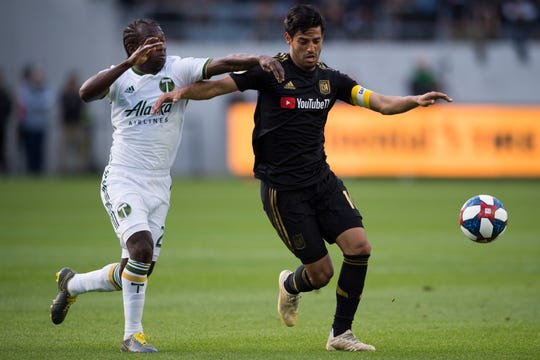 Los Angeles FC forward Carlos Vela (10) and Portland Timbers midfielder Diego Chara (21) battle for the ball during the first half at Banc of California Stadium.