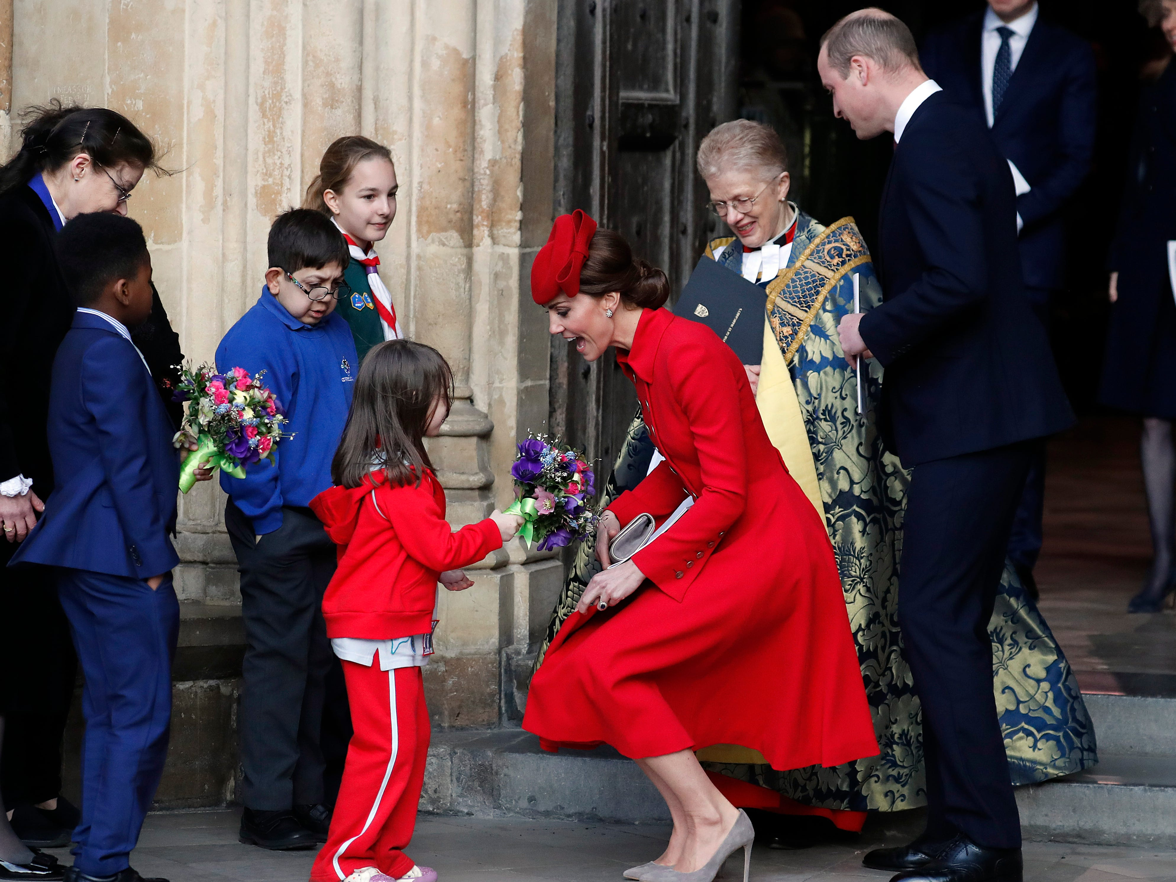 Duchess Kate grins as she kneels down to accept a bouquet of flowers from a young girl after attending a Commonwealth Day service at London's Westminster Abbey on March 11, 2019.