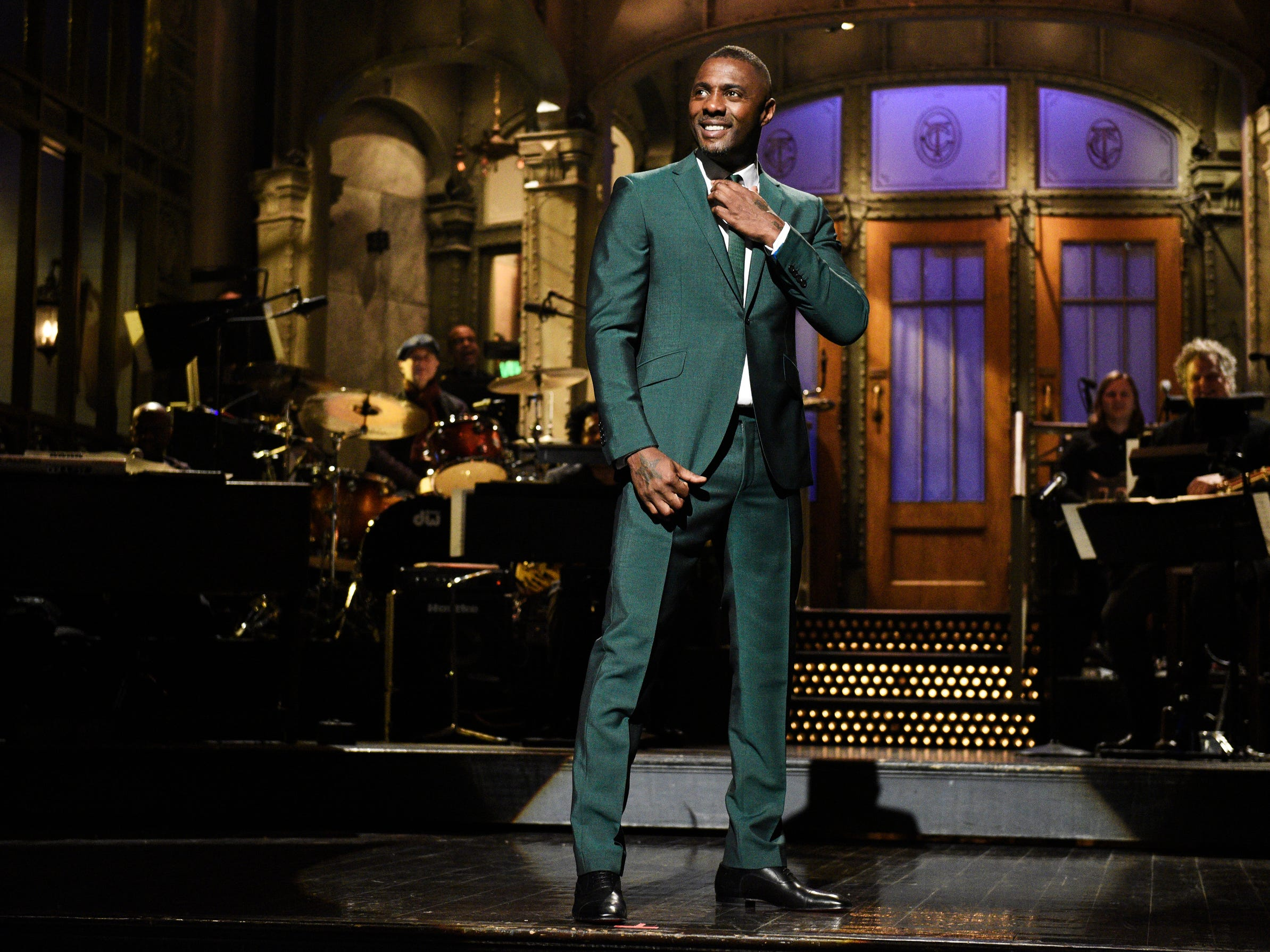 "Idris Elba, who hosted the March 9 episode of 'SNL,"" shows off his snazzy green suit during the monologue."