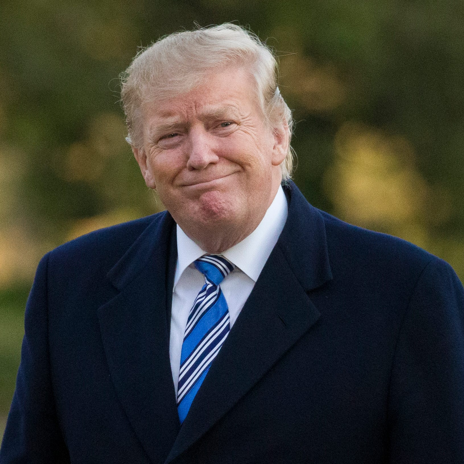 President Donald Trump smiles as he walks on the South Lawn after stepping off Marine One at the White House, March 10, 2019, in Washington.