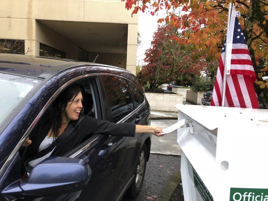 A voter places her ballot in a drop box Nov. 6 in Lake Oswego, Ore.