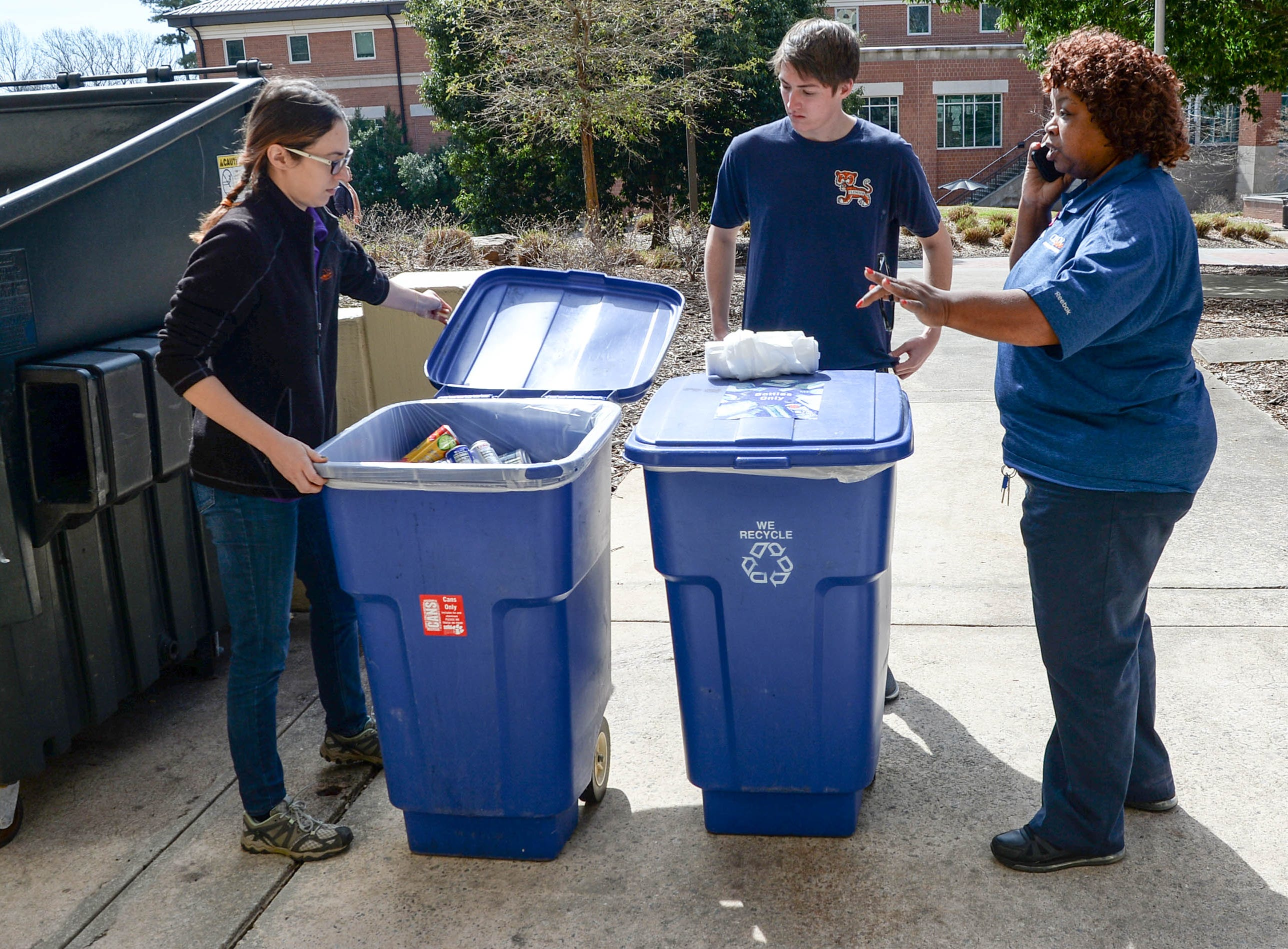 Clemson University recycle coordinator Brittany Morra, left, and Caleb Todd, middle, communicate with a school dormitory facilities supervisor Shirley Kemp, right, as they get ready to study recycled and unsorted trash bags, part of a study of student recycle habits in March. The waste audit, part of the annual RecycleMania competition with Universities across the country found from a sample study that Clemson students who recycle plastic and cans are good at doing so, said Morra, leading the study on the lawn outside Manning and Byrnes Hall tower dormitories.