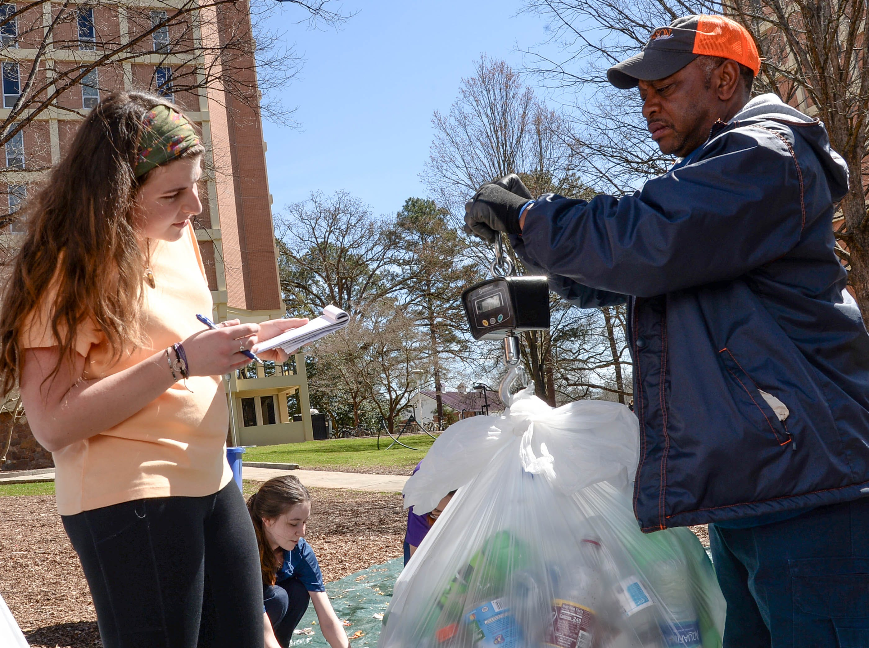 Clemson University student Olivia McQuarrie, left, writes down the weight of plastic in a bag held by facilities department employee Roy Wilson during a study of student recycle habits March 12. The waste audit, part of the annual RecycleMania competition with Universities across the country found from a sample study that Clemson students who recycle plastic and cans are good at doing so, said Morra, leading the study on the lawn outside Manning and Byrnes Hall tower dormitories.
