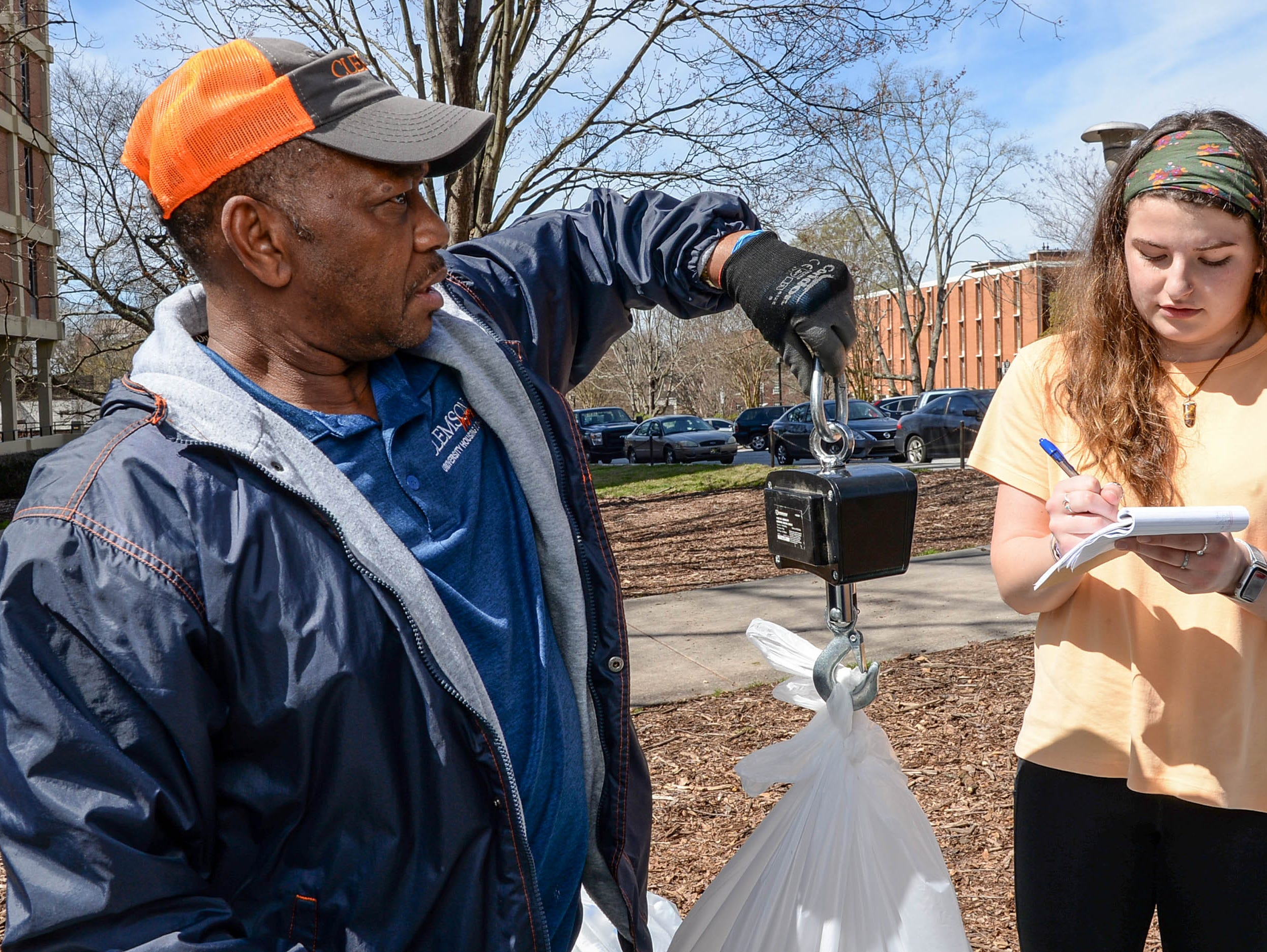 Clemson University student Olivia McQuarrie, right, writes down the weight of plastic in a bag held by facilities department employee Roy Wilson during a study of student recycle habits March 12. The waste audit, part of the annual RecycleMania competition with Universities across the country found from a sample study that Clemson students who recycle plastic and cans are good at doing so, said Morra, leading the study on the lawn outside Manning and Byrnes Hall tower dormitories.